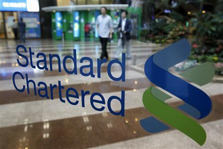 Workers at Standard Chartered First Bank walk in the lobby of the bank's headquarters in Seoul in this June 27, 2011 file photo. REUTERS/Jo Yong-Hak/Files (SOUTH KOREA - Tags: BUSINESS)