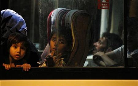 New Syrian refugees look out from their bus as they arrive at a refugee camp in the Turkish border town of Reyhanli in Hatay province August 6, 2012. REUTERS/Umit Bektas
