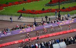 Атлеты проезжают мимо Букингемского дворца во время соревнований по триатлону в Лондоне 4 августа 2012 года. На Олимпийских играх в Лондоне во вторник будет разыгран 21 комплект наград. REUTERS/Emmanuel Dunand/Pool