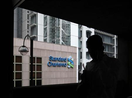 A man walks on a footbridge connected to the Standard Chartered headquarters in Hong Kong August 7, 2012. REUTERS/Bobby Yip