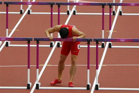 China's Liu Xiang kisses the last hurdle in his lane after crashing into the first hurdle and failing to finish his men's 110m hurdles round 1 heat at the London 2012 Olympic Games at the Olympic Stadium August 7, 2012. Liu crashed out of the heats in the 110 metres hurdles in an echo of his injury-induced withdrawal from the same stage of the Beijing Games four years ago. REUTERS/David Gray