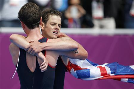 First placed Britain's Alistair Brownlee (L) embraces Jonathan Brownlee who placed third after the men's triathlon final during the London 2012 Olympic Games at Hyde Park August 7, 2012. REUTERS/Jorge Silva