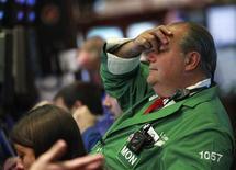 Трейдеры на торгах Нью-Йоркской фондовой биржи 6 августа 2012 года. Американские рынки акций открылись ростом во вторник продолжив подъем третью сессию подряд, за счет новых надежд на скорые дополнительные антикризисные шаги Европейского Центробанка. REUTERS/Brendan McDermid