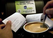 A customer checks the IVU Loto on his printed receipt at a coffee shop in San Juan July 31, 2012. REUTERS/Ana Martinez