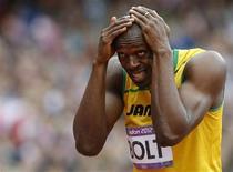 """Usain Bolt sorri e cobre a cabeça antes das eliminatórias dos 200m nos Jogos Olímpicos de Londres. Bolt, o homem mais rápido do mundo, planeja """"contrabandear"""" a corda com que pula para treinar no Estádio Olímpico depois que um fiscal a confiscou quando ele rumava para a final dos 100 metros. 07/08/2012 REUTERS/Phil Noble"""