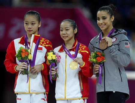 China's Deng Linlin (C) celebrates winning a gold medal in the women's gymnastics balance beam victory ceremony with silver medallist China's Sui Lu and bronze medallist Alexandra Raisman (R) of the U.S. in the North Greenwich Arena during the London 2012 Olympic Games August 7, 2012. REUTERS/Mike Blake