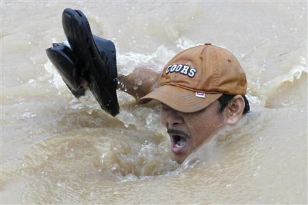 A man holds his shoes as he swims in floodwaters along a road in Marikina, Metro Manila August 7, 2012. Deadly torrential rains submerged much of the Philippine capital and surrounding areas on Tuesday, forcing nearly 270,000 people to flee their homes with more flooding expected in the north of the country as a tropical storm passes through the region, officials said. REUTERS/Erik De Castro