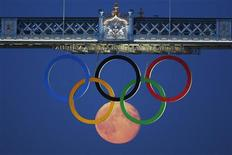 The full moon rises through the Olympic Rings hanging beneath Tower Bridge during the London 2012 Olympic Games August 3, 2012. Standout images from London have ranged from underwater shots of Michael Phelps ploughing through the pool, to long-range images of Prince William hugging his wife Kate at the cycling, to artistic images of the moon below Tower Bridge rising through the Olympics rings. Picture taken August 3, 2012. REUTERS/Luke MacGregor