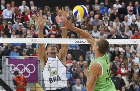 Brazil's Emanuel (L) block a spike from Latvia's Martins Plavins during the men's beach volleyball semifinal match at Horse Guards Parade during the London 2012 Olympic Games August 7, 2012. REUTERS/Suzanne Plunkett