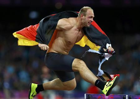 Germany's Robert Harting jumps over a hurdle as he celebrates winning the men's discus throw final during the London 2012 Olympic Games at the Olympic Stadium August 7, 2012. Harting won gold ahead of Iran's Ehsan Hadadi who took silver and Estonia's Gerd Kanter who won bronze. REUTERS/Eddie Keogh