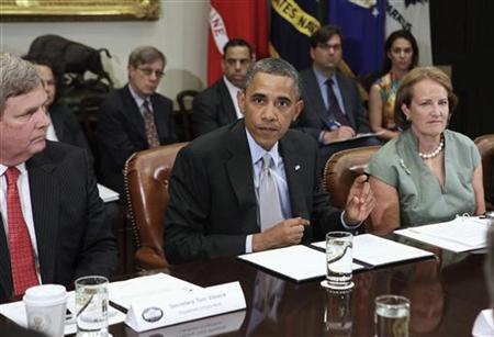 Secretary of Agriculture Tom Vilsack (L) listens to President Barack Obama as he talks to the media during a meeting with the White House Rural Council to discuss ongoing efforts in response to the drought, at the White House in Washington, August 7, 2012. REUTERS/Yuri Gripas