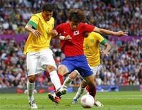 O brasileiro Thiago Silva (esquerda) desafia o sul-coreano Ji Dong-won durante a semi-final de futebol nos Jogos Olímpicos de 2012 em Manchester, no Reino Unido. 7/08/2012 REUTERS/David Moir