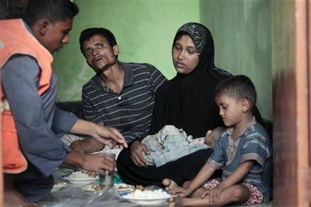 A member of the Bangladesh Coast Guard serves food to Mohammad Rafique and Amena Akter, both Rohingyas from Myanmar, in Teknaf June 19, 2012. REUTERS/Andrew Biraj