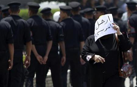 A woman walks with a paper that reads ''Leave, Mursi'' during a funeral for soldiers, who were killed during an attack at a checkpoint along the Sinai border with Israel by unknown gunmen, at the tomb of the late former President Anwar al-Sadat and the Unknown Soldier monument in Cairo August 7, 2012. REUTERS/Amr Abdallah Dalsh