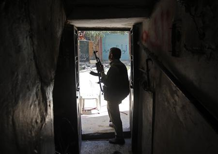 A Free Syrian Army fighter holds his gun as he looks at a street from a house during clashes with Syrian Army in the Salaheddine neighbourhood of central Aleppo August 7, 2012. REUTERS/Goran Tomasevic