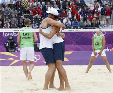 Brazil's Alison (centre L) and Emanuel celebrate a point against Latvia's Martins Plavins and Janis Smedins during their men's beach volleyball semifinal match at Horse Guards Parade during the London 2012 Olympic Games August 7, 2012. REUTERS/Suzanne Plunkett