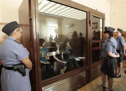 Nadezhda Tolokonnikova (L), Yekaterina Samutsevich (R) and Maria Alyokhina, members of female punk band ''Pussy Riot'', sit in the defendant's cell before a court hearing in Moscow August 8, 2012. REUTERS/Sergei Karpukhin