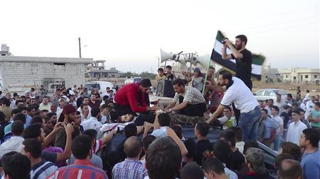 Residents gather at the body of Ahmed Assaf, whom activists say was killed by shelling by forces loyal to Syria's President Bashar al-Assad, during his funeral in Binsh near Idlib, August 7, 2012. REUTERS/Shaam News Network/Handout