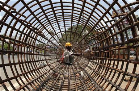A worker tightens steel rebars at a construction site of a metro station in Chennai July 7, 2012. REUTERS/Babu/Files