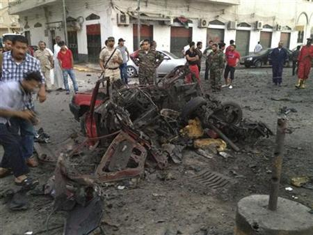 Members of the military and bystanders look at debris after a car bomb exploded near the offices of the military police in Tripoli August 4, 2012. REUTERS/Stringer