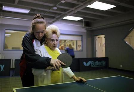 Holocaust survivor Betty Stein, 92, (R) is helped by coach Irina Jestkova as she plays ping pong at a program for people with Alzheimer's and dementia at the Arthur Gilbert table tennis center in Los Angeles, California June 15, 2011. REUTERS/Lucy Nicholson