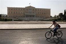Music saleswoman Elena Koniaraki, 39, rides her bicycle in front of the parliament on the way to work in Athens July 6, 2012. REUTERS/Yorgos Karahalis