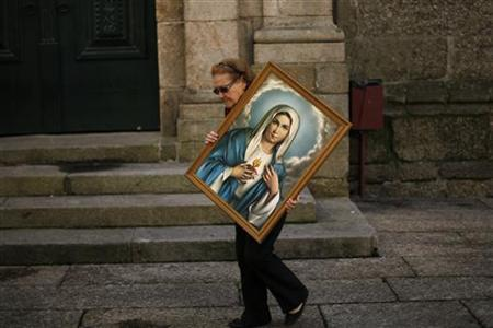 A woman carries a portrait of the Virgin Mary at the Oliveira square in Guimaraes August 26, 2011. REUTERS/Rafael Marchante/Files