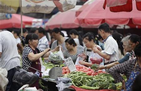 Customers buy vegetables at a market in central Beijing, July 9, 2012. REUTERS/Jason Lee