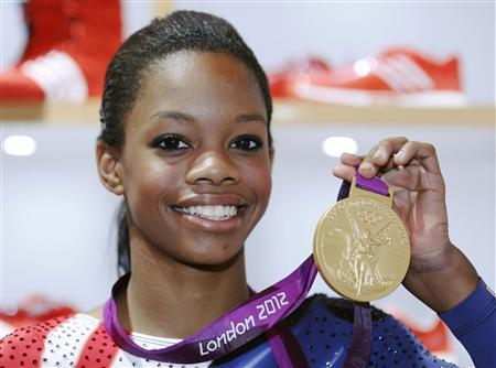 U.S. gymnast Gabby Douglas, 16, poses with her gold medal during a news conference at the 2012 London Olympic Games August 8, 2012. REUTERS/Luke MacGregor