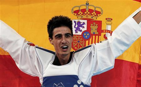 Spain's Joel Gonzalez Bonilla celebrates with a national flag after winning his men's -58kg gold medal taekwondo match against South Korea's Lee Dae-hoon during the London 2012 Olympic Games at the ExCeL arena August 8, 2012. REUTERS/Stefano Rellandini