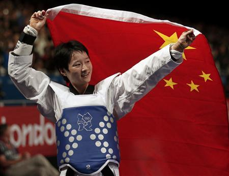 China's Wu Jingyu celebrates with a national flag after winning her women's -49kg gold medal taekwondo match against Spain's Brigitte Yague Enrique during the London 2012 Olympic Games at the ExCeL arena August 8, 2012. REUTERS/Stefano Rellandini
