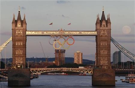 The full moon rises near the Olympic Rings hanging beneath Tower Bridge during the London 2012 Olympic Games August 1, 2012. REUTERS/Luke MacGregor