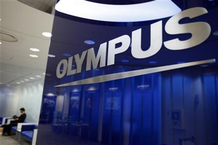 A man sits near a logo of Japan's Olympus Corp at the company headquarters in Tokyo June 19, 2012. REUTERS/Yuriko Nakao