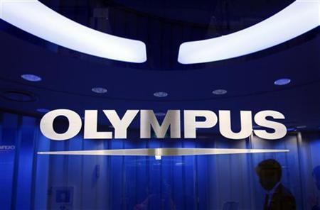 A man passes behind a logo of Japan's Olympus Corp at the company headquarters in Tokyo June 19, 2012. REUTERS/Yuriko Nakao