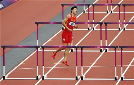 China's Liu Xiang hops back to his lane after crashing and failing to finish his men's 110m hurdles round 1 heat during the London 2012 Olympic Games at the Olympic Stadium August 7, 2012. REUTERS/David Gray