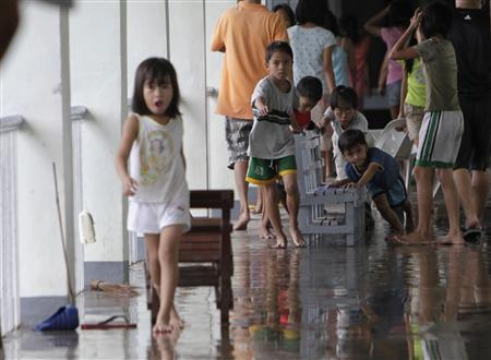 Students who are evacuated and transferred to their damaged campus help clean and restore their school in Malabon, Metro Manila August 9, 2012. REUTERS/John Javellana