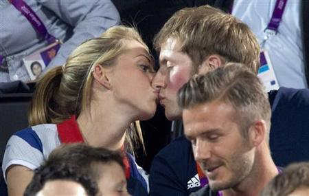 Gold medal-winning British cyclists Laura Trott and Jason Kenny kiss whilst sitting in front of footballer David Beckham during the women's beach volleyball final at Horse Guards Parade during the London 2012 Olympic Games August 8, 2012. REUTERS/Neil Hall