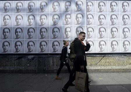 People walk past posters of gold medal winning British athlete Jessica Ennis, the day after she won the heptathlon event at the London 2012 Olympic Games August 5, 2012. REUTERS/Dylan Martinez