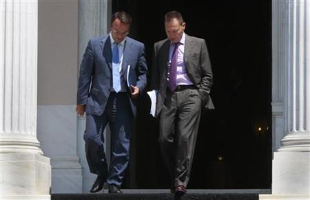 Greek Finance Minister Yannis Stournaras (R) and his alternate minister of finance Christos Staikouras leave the Prime Minister's office in Athens July 17, 2012. REUTERS/John Kolesidis