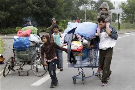 Roma families push shopping carts with their belongings as they are evacuated from an illegal camp in Villeneuve d'Ascq, August 9, 2012. REUTERS/Pascal Rossignol
