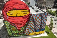 Pessoas caminham diante de mural pintado pelos grafiteiros brasileiros Os Gemeos, em Boston. O colorido mural que domina um parque em frente da principal estação ferroviária de Boston, na costa leste dos Estados Unidos, provoca alguma controvérsia. 08/08/2012 REUTERS/Dominick Reuter