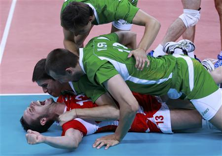 Bulgaria's (bottom to top) Teodor Salparov, Nikolay Penchev, Viktor Yosifov, and Dobromir Dimitrov celebrate winning their men's quarterfinal volleyball match against Germany at Earls Court during the London 2012 Olympic Games August 8, 2012. REUTERS/Olivia Harris