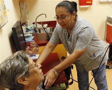 Medical assistant Maria Cortez (R) checks the blood pressure of a patient at the La Clinica Del Pueblo community health clinic in Washington August 2, 2012. REUTERS/Gary Cameron