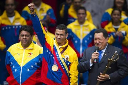 Venezuela's President Hugo Chavez (R) presents Venezuela's fencer, Olympic gold medallist Ruben Limardo Gascon (C), with a replica of the sword of national hero Simon Bolivar during a ceremony in Caracas August 7, 2012. REUTERS/Carlos Garcia Rawlins