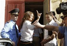 Belarussian journalist Irina Kozlik (C) is escorted by police officers before a court session in Minsk, August 9, 2012. REUTERS/Vasily Fedosenko