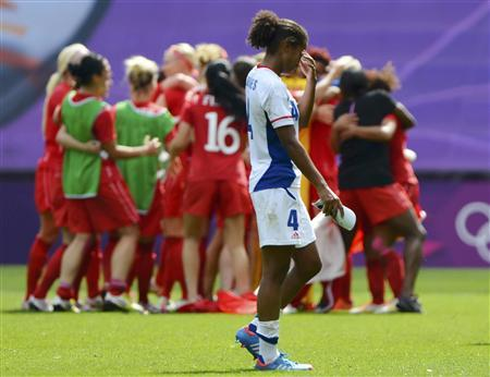 France's Laura George (4) walks off the pitch as Canada celebrates winning the women's bronze medal soccer match in Coventry at City of Coventry Stadium at the London 2012 Olympic Games August 9, 2012. REUTERS/Paul Hackett