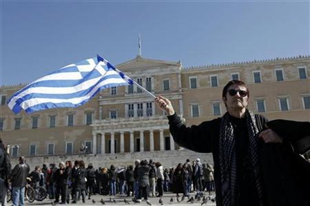 A woman raises a Greek flag during an anti-austerity rally in front of the parliament in Athens February 19, 2012. REUTERS/Yiorgos Karahalis/Files