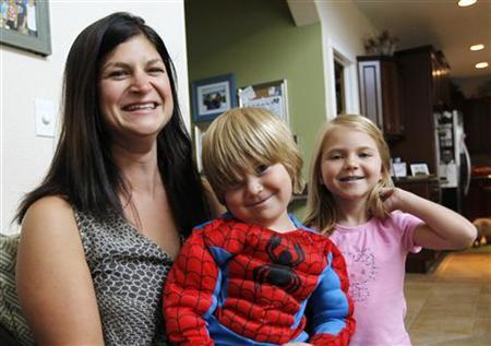 Sarah Formato, a 31-year-old stay-at-home mom, poses with her children Finn (C), 3, dressed in a Spiderman costume and Hollyn, 5, at her home in Aurora, Colorado July 30, 2012. REUTERS/Rick Wilking