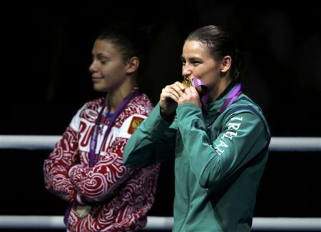 Katie Taylor of Ireland kisses her gold medal as silver medallist Sofya Ochigava of Russia looks on during the medal ceremony for the Women's Light (60kg) boxing competition at the London Olympic Games August 9, 2012. REUTERS/Damir Sagolj