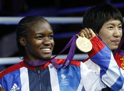 Britain's Nicola Adams poses with her gold medal during the presentation ceremony after defeating China's Ren Cancan (R) in their Women's Fly (51kg) gold medal boxing match at the London Olympic Games August 9, 2012. REUTERS/Murad Sezer